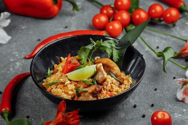 Ryż tajski z kurczakiem. tajskie danie z ryżu, kurczaka, cebuli jałtańskiej, kukurydzy, ananasa, pomidora, sosu sojowego, pasty chili, kolendry, limonki, papryczki chili przyprawy do zielonej cebuli