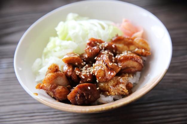 Ryż teriyaki z grilla z kurczaka na tle drewna, japońskie jedzenie