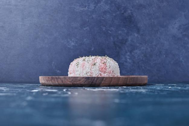 Ryż udekorować cytryną na drewnianym talerzu.