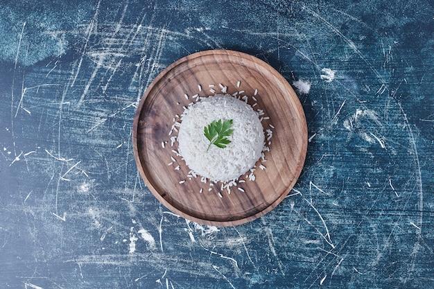 Ryż udekorować natką pietruszki na drewnianym talerzu.