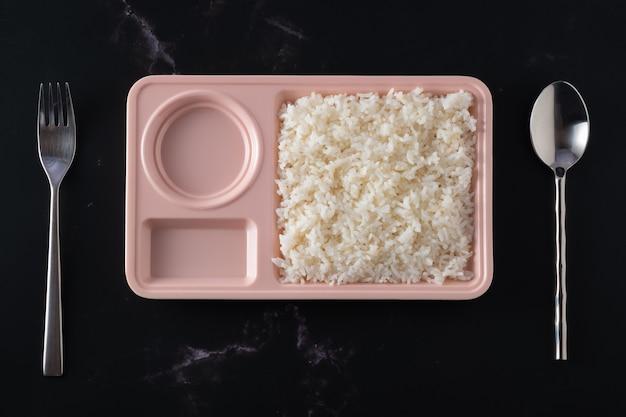 Ryż w pastelowych miseczkach na czarnym tle, dwa puste otwory, jedzenie z góry, widelec po lewej stronie talerza i łyżka po prawej.