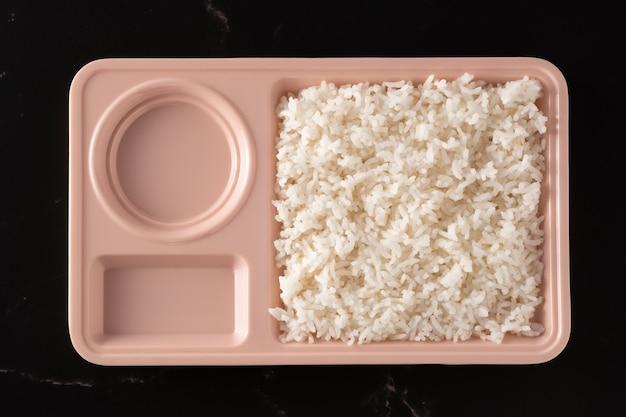 Ryż w pastelowych miseczkach na czarnym tle, dwa puste otwory, jedzenie z góry.