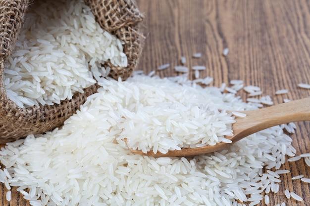 Ryż w workach i na drewnianej łyżce do postawienia na drewnianym stole