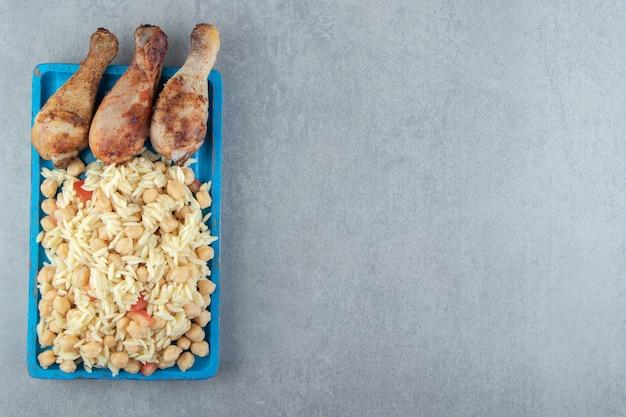 Ryż z ciecierzycą i udkami z kurczaka na niebieskim talerzu.