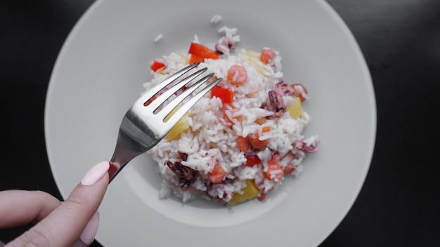 Ryż z krewetkami i ananasem, tajskim lub chińskim jedzeniem na białym talerzu. widelec w dłoni