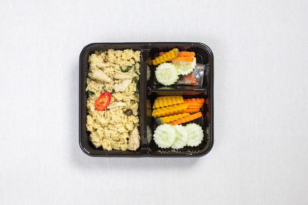 Ryż z kurczaka green curry w czarnym plastikowym pudełku, na białym obrusie, pudełku na żywność, tajskim jedzeniu.