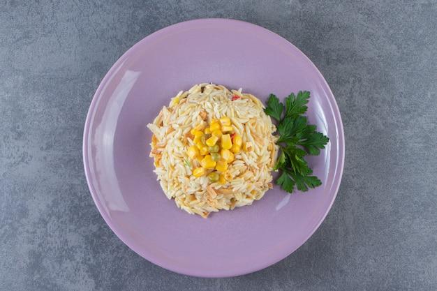 Ryż z makaronem na talerzu obok soli, na niebieskiej powierzchni.