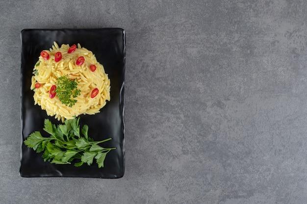 Ryż z plasterkami pieprzu i zieleni na czarnej płycie. zdjęcie wysokiej jakości
