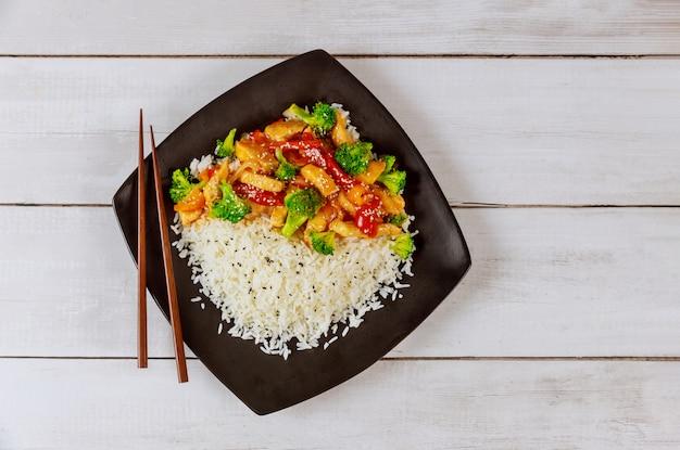 Ryż z smażonym kurczakiem i warzywami na czarnym kwadratowym talerzu