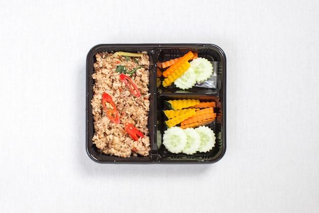 Ryż zmieszany z bazylią i mieloną wieprzowiną włożony w czarne plastikowe pudełko, ułożony na białym obrusie, pudełku na żywność, tajskim jedzeniu.
