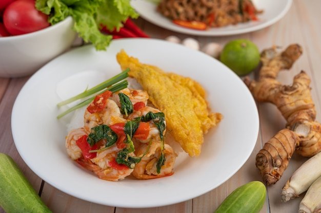 Ryż zwieńczony krewetkami i omlet na białym talerzu.