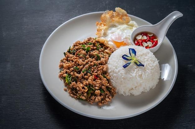 Ryż zwieńczony smażoną wieprzowiną i bazylią na drewnianym. tajskie jedzenie