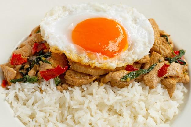 Ryż zwieńczony smażonym kurczakiem i świętą bazylią