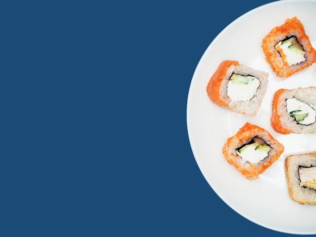 Ryżowe rolki na round bielu talerzu na błękitnym tle