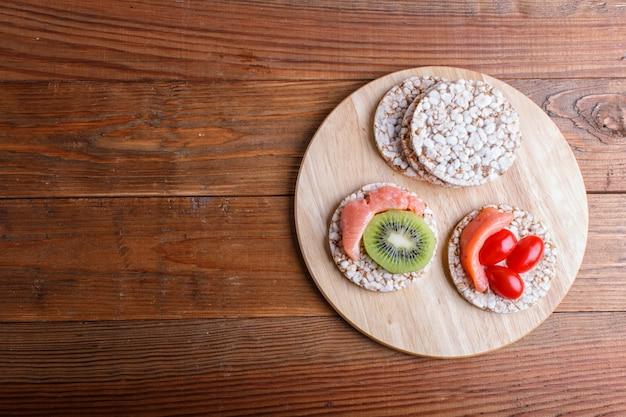 Ryżowi torty z łososiem, kiwi i czereśniowymi pomidorami na drewnianym tle.