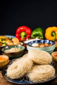 Ryżowi wermiszel na talerzu z tajlandzkim tradycyjnym jedzeniem przeciw czarnemu tłu