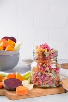 Ryżowy fusilli suchy makaron z warzyw w szklanym słoju. jego naturalne barwniki roślinne: seler, burak, marchew, dynia, pasternak. zdrowa żywność koncepcja bezglutenowa