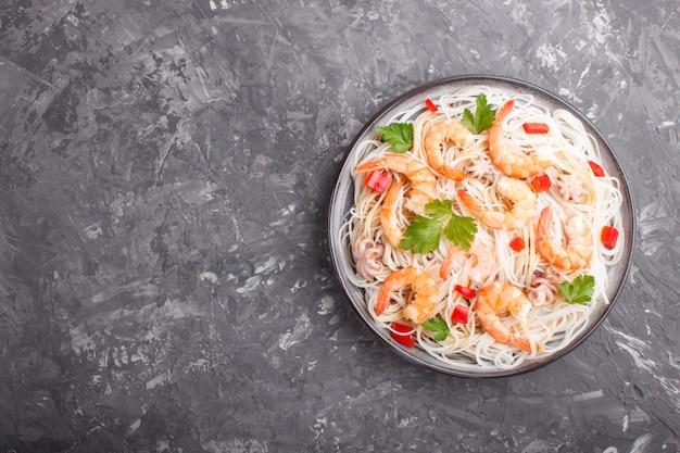 Ryżowy makaron z krewetkami lub krewetkami i małymi ośmiornicami na szarym ceramicznym talerzu na czarnym betonowym tle