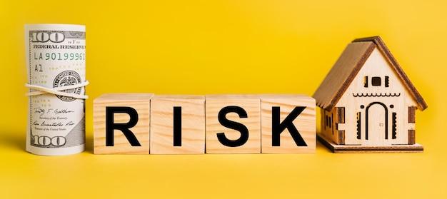Ryzyko z miniaturowym modelem domu i pieniędzmi na żółtym tle. pojęcie biznesu, finansów, kredytu, podatków, nieruchomości, domu, mieszkania