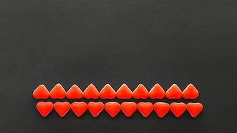 Rzędy czerwoni kierowi kształtów cukierki na czarnym tle