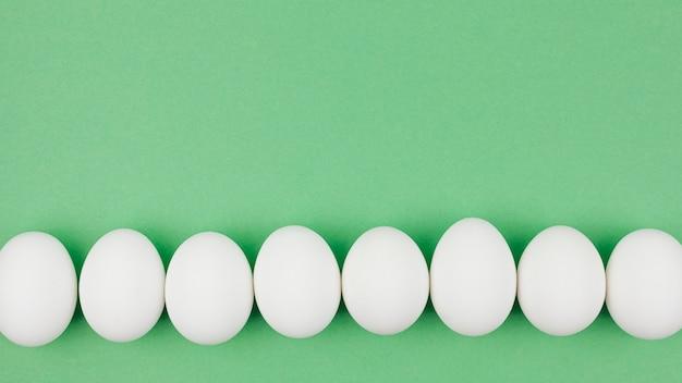 Rząd biali kurczaków jajka na zielonym stole