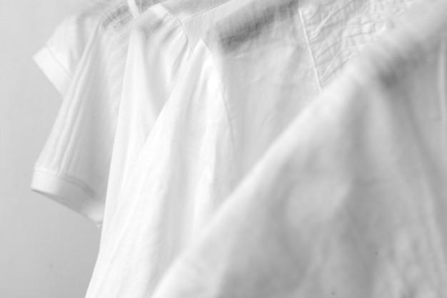 Rząd białych bawełnianych ubrań wisi na czarnych wieszakach na stojaku w sklepie. szafa minimalistyczna kobieta. zbliżenie.