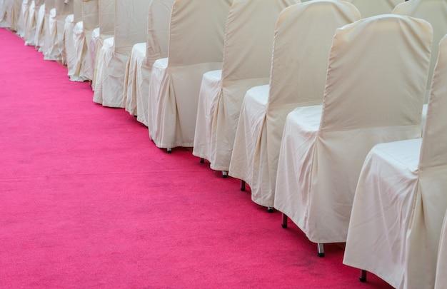 Rząd białych tkanin krzesła na czerwonym chodniku