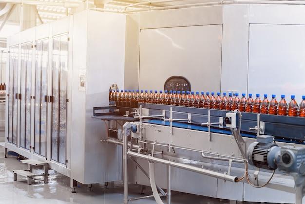 Rząd butelek z brązowego piwa na linii przenośnika do napełniania piwa
