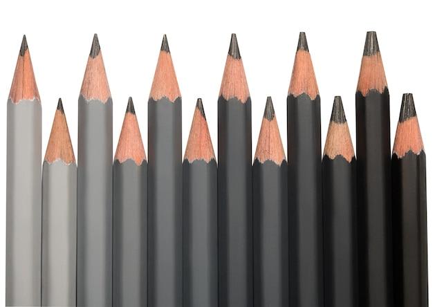 Rząd czarnych ołówków grafitowych o różnej twardości w kolorze od jasnoszarego do czarnego.