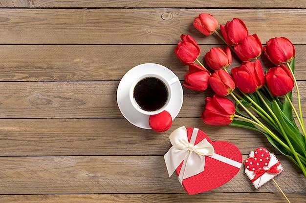 Rząd czerwoni tulipany, filiżanka czarnej kawy americano