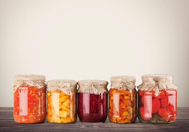 Rząd domowych warzyw w puszkach letnich, szklane słoiki na białym tle
