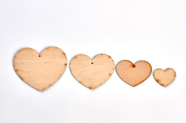 Rząd drewnianych wycinanek w kształcie serca. cztery drewniane serca na białym tle. ręcznie robione dekoracje na walentynki.