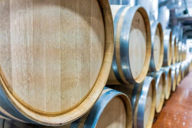 Rząd dużych beczek na wino z francuskiego dębu w magazynie wina