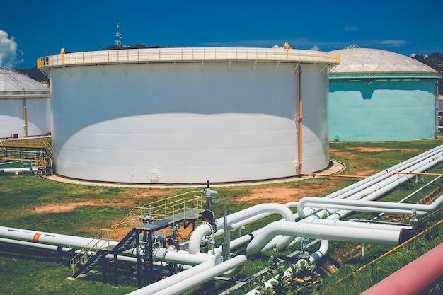 Rząd dużych białych zbiorników na część zamienną stacji benzynowej i rafinerii.
