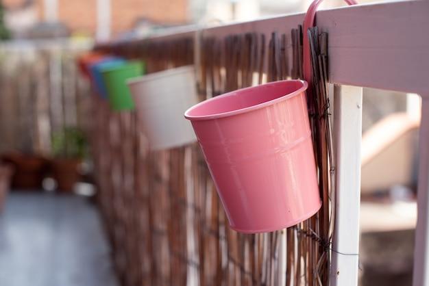 Rząd kolorowych doniczek wiszących na balustradzie tarasu