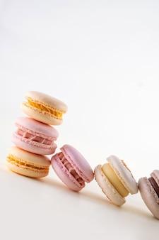 Rząd kolorowych pastelowych francuskich makaroników lub makaroników na białym i różowym tle