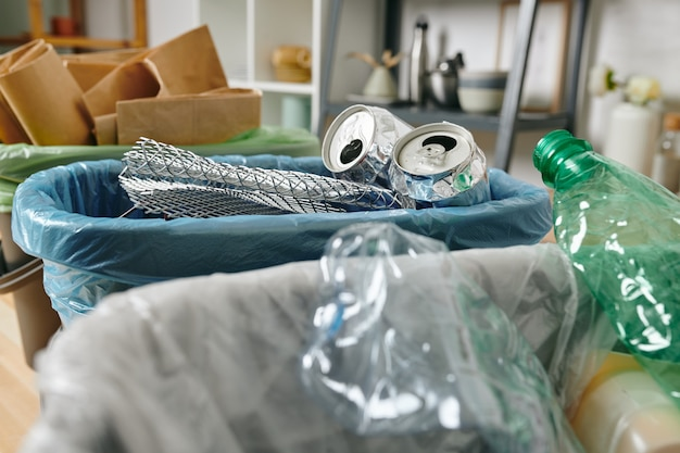 Rząd koszy na śmieci z pustymi puszkami, plastikowymi butelkami i złożonym papierem