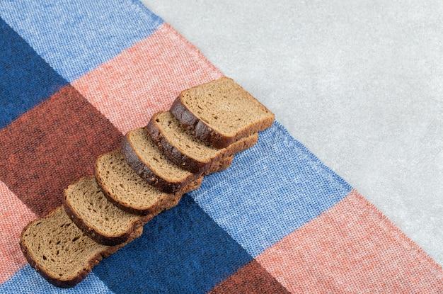 Rząd kromek ciemnego chleba na obrusie.