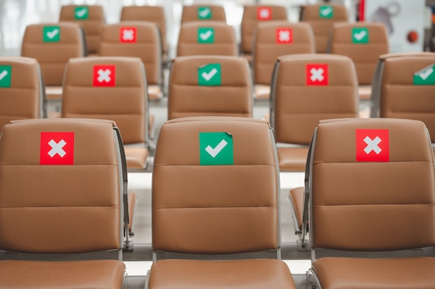 Rząd krzesła ze znakiem dystansu społecznego, aby zapobiec rozprzestrzenianiu się wirusa podczas epidemii koronawirusa