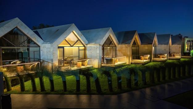 Rząd małych nowoczesnych domów do wynajęcia na noc. oświetlenie i zielony trawnik przed nimi