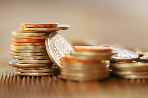 Rząd monety na drewnianym tle dla finanse i oszczędzania pojęciu
