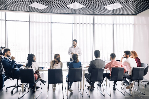 Rząd nierozpoznawalni ludzie biznesu siedzą w sala konferencyjnej przy wydarzeniem biznesowym.