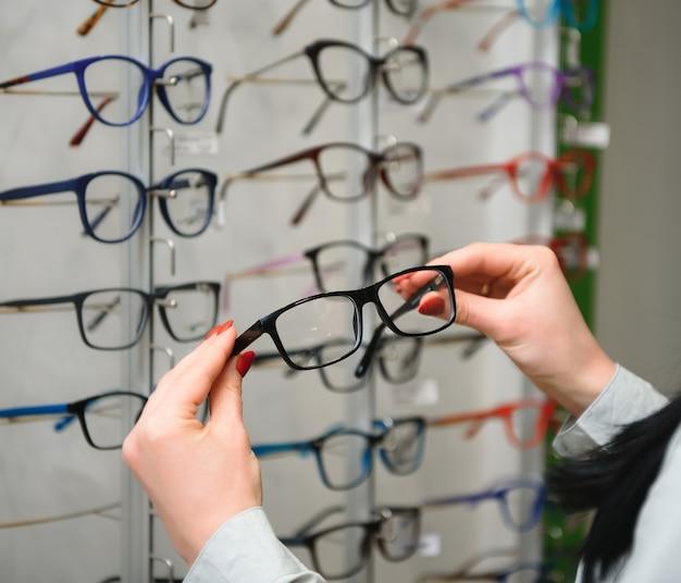 Rząd okularów u optyka. sklep z okularami. stań z okularami w sklepie optyki. ręka kobiety wybiera okulary. korekta wzroku.