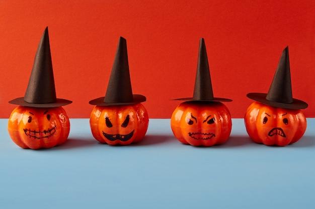 Rząd ozdobnych dyni w czarnych kapeluszach na niebiesko-pomarańczowym tle. koncepcja wakacje halloween.