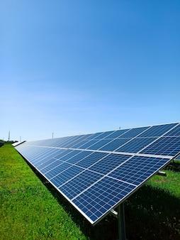Rząd paneli słonecznych stoi na zielonym polu, na tle błękitnego nieba. symbol czystej energii, troski o środowisko, koncepcja.