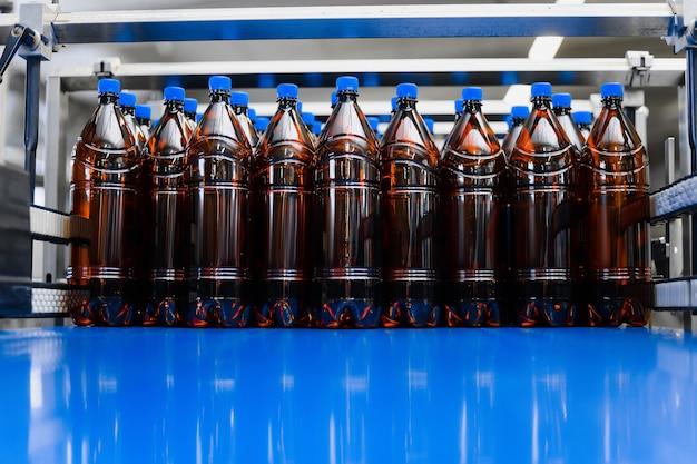 Rząd plastikowych butelek piwa na przenośniku taśmowym.