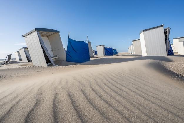 Rząd pojedynczych białych szatni i przebieralni na piaszczystej plaży