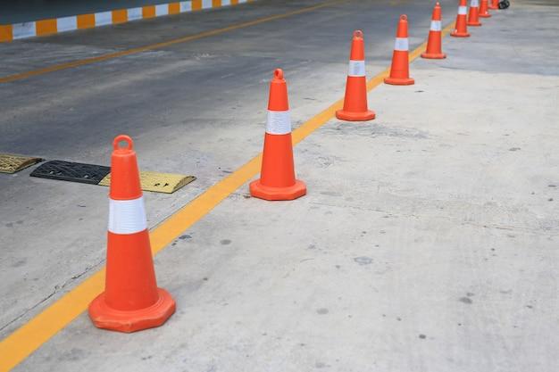 Rząd pomarańczowy gumowy ruch drogowy rożek umieszczający w drodze.