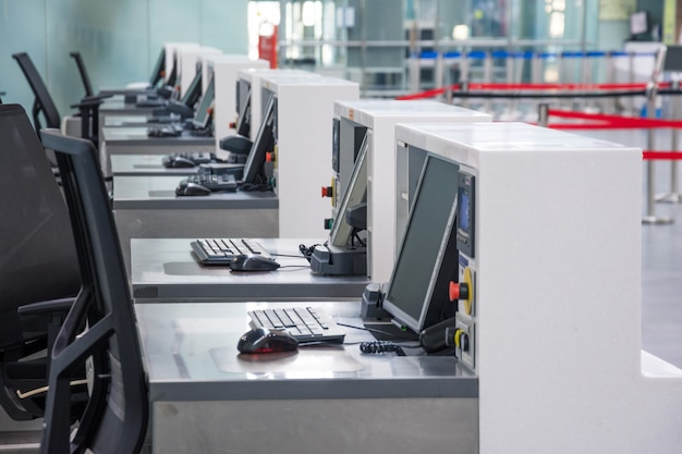 Rząd pustych stanowisk odprawy z monitorami komputerowymi na lotnisku.