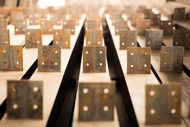 Rząd rolek aluminium leży w hali produkcyjnej zakładu.